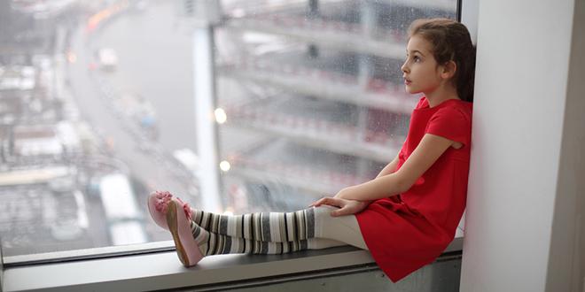 Девојчица седи крај прозора. облачан дан