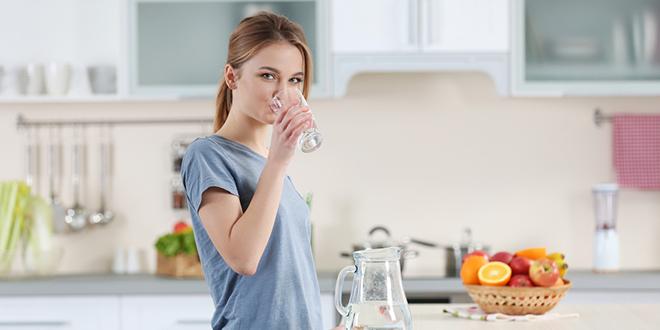 Mlada žena pije vodu iz čaše u kuhinji