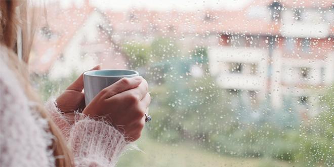 Млада жена ужива у јутарњем чају и гледа кроз прозор