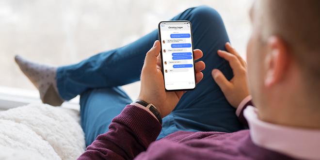 Muškarac četuje sa prijateljima u aplikaciji Facebook Messenger na mobilnom telefonu