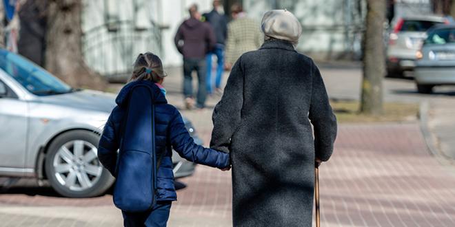 Starija žena sa štapom i devojčica šetaju ulicom