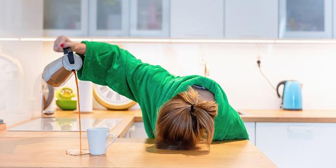 Уморна жена покушава да попије јутарњу кафу у кухињи