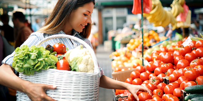 Žena kupuje povrće na pijaci