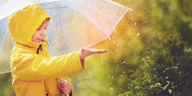 Dete sa kišobranom u parku hvata kapljice kiše