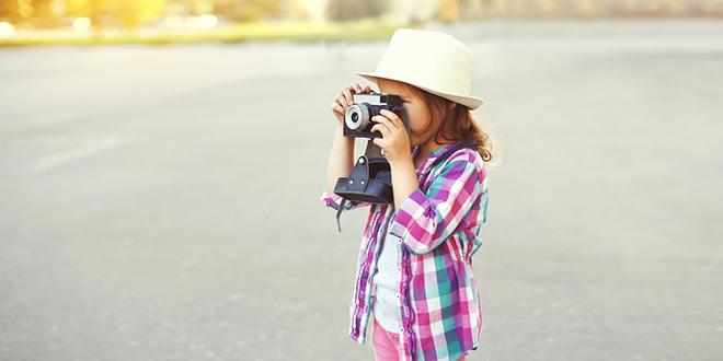 Devojčica retro foto-aparatom slika na otvorenom