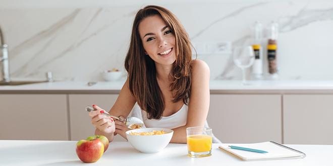 Девојка доручкује кукурузне пахуљице у кухињи