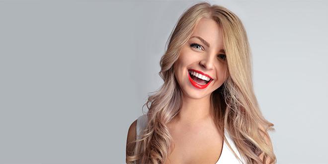 Лепа девојка са црвеним кармином и блиставо белим зубима се смеје