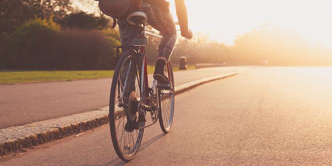 Млада девојка вози бицикл у парку