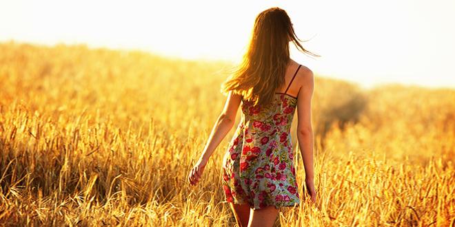 Mlada žena hoda u žitnom polju