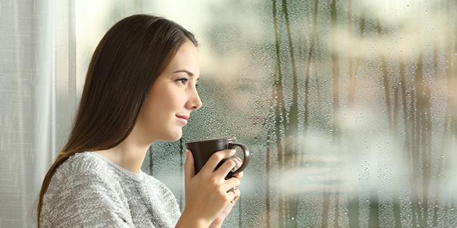 Žena stoji kraj prozora i posmatra kišovit dan