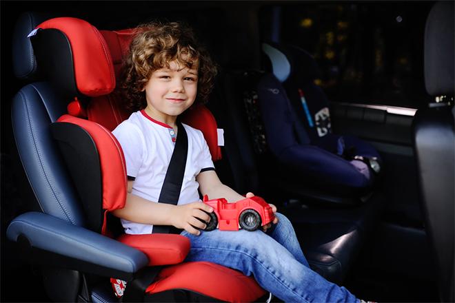 Dečak sedi u dečjem auto-sedištu vezan sigurnosnim pojasom