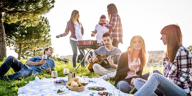 Група пријатеља се забавља док једе и пије на пикнику