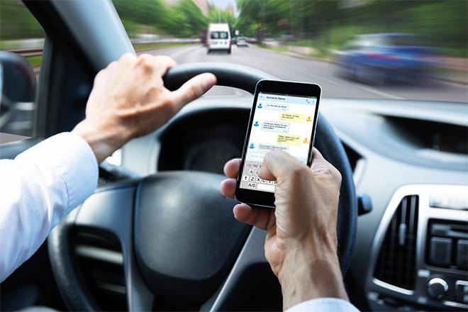 Muškarac koristi mobilni telefon tokom vožnje automobila
