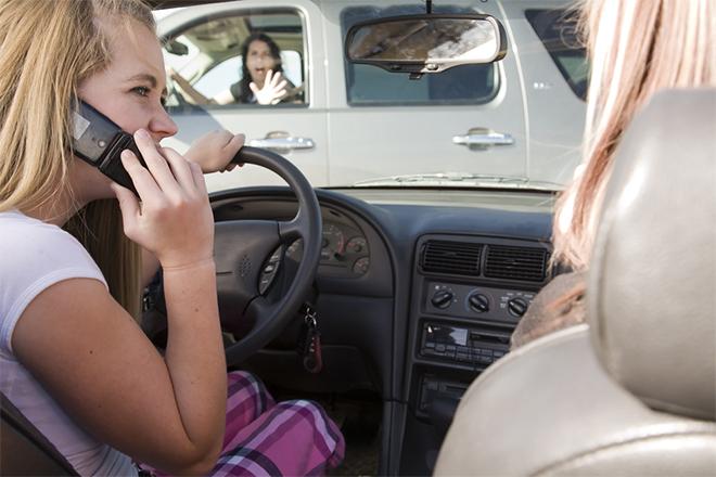 Tinejdžerka razgovara mobilnim telefonom dok vozi i ide ka drugom automobilu