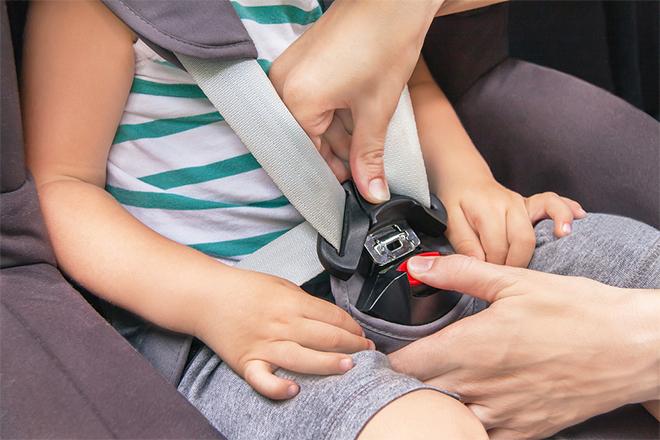 Žena pričvršćuje sigurnosni pojas detetu