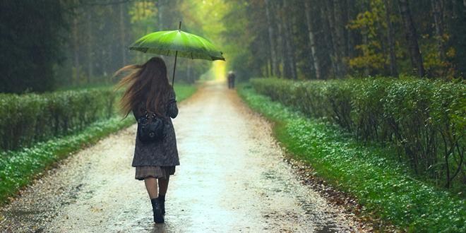 Devojka sa zelenim kišobranom šeta po kiši