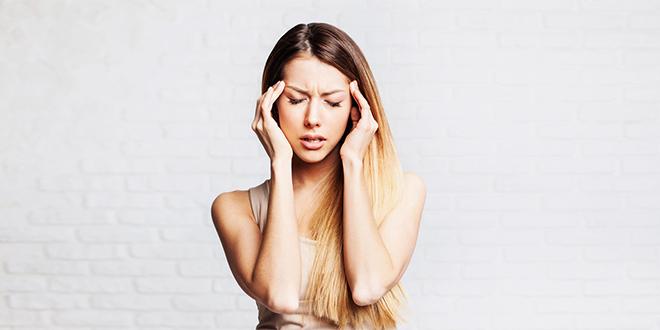Mlada devojka oseća glavobolju