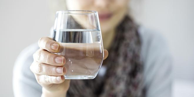 Жена држи стаклену чашу са водом