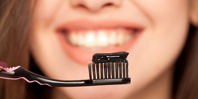 Devojka drži crnu četkicu i crnu pastu za zube
