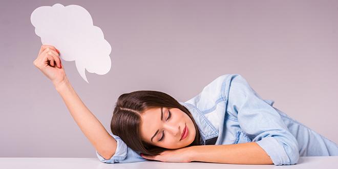 Devojka spava na stolu držeći u ruci tekstualni oblačić