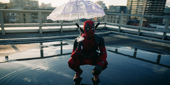 Kosplejer obučen u kostim Deadpool-a drži kišobran