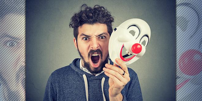 Ljut muškrarac drži masku nasmejanog klovna