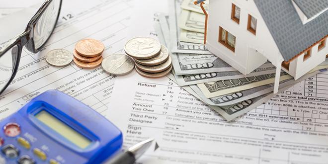 Maketa kuće. papiri za porez, novac, kalkulator, naočare za vid