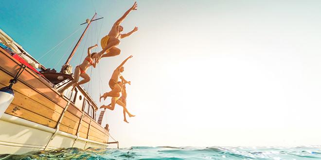 Млади људи скачу са једрилице у океан