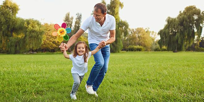 Otac se zabavlja i trči sa ćerkom u prirodi