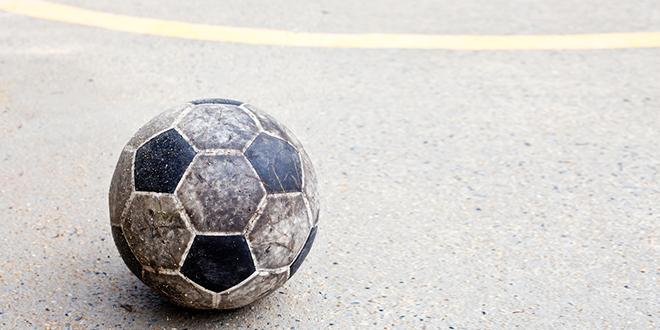 Stara fudbalska lopta na betonskom terenu