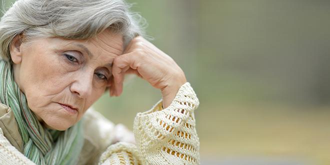 Zamišljena starija žena sedi u parku