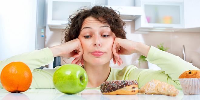 Žena se razmišlja šta će pojesti između voća i slatkiša
