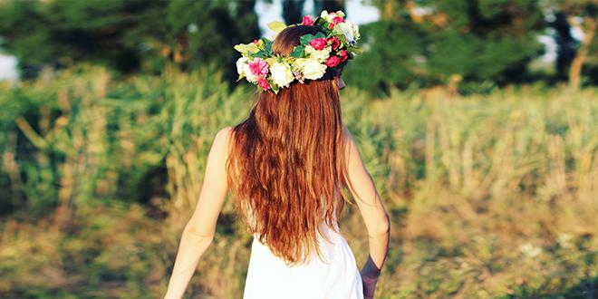 Žena u beloj haljini stoji u polju sa cvetnom krunom