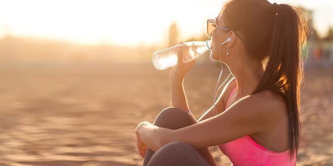 Devojka pije vodu posle napornog treninga