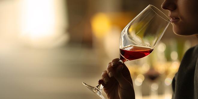 Žena pije crveno vino u staklenoj čaši