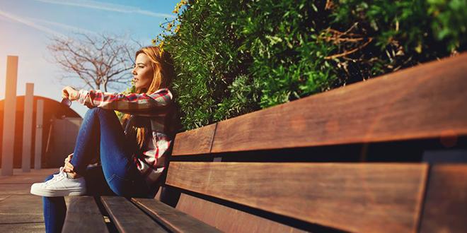 Devojka sedi na klupi u parku
