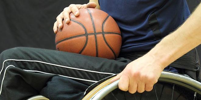 Momak u kolicima drži košarkašku loptu