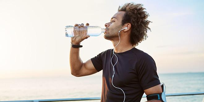 Muškarac pije vodu iz plastične flašice