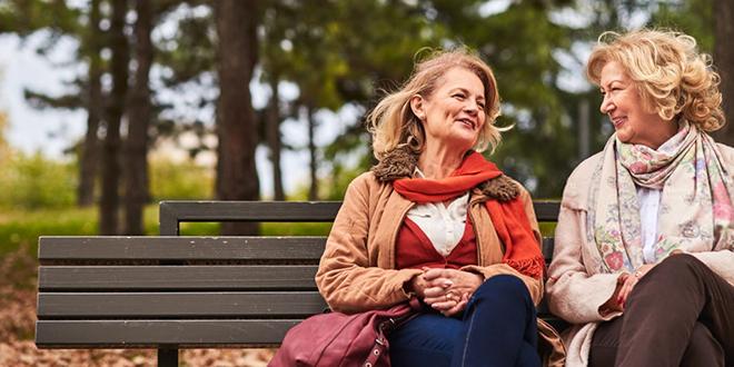 Две старије жене седе у парку и разговарају