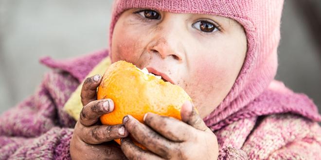 Siromašno dete jede voće uprljanim rukama