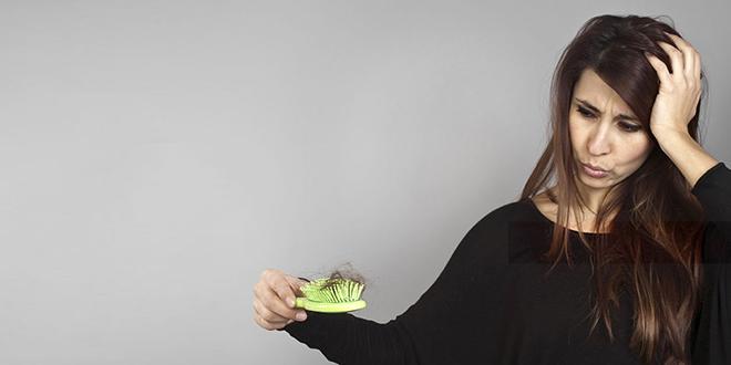 Жена држи чешаљ за косу пун испалих власи