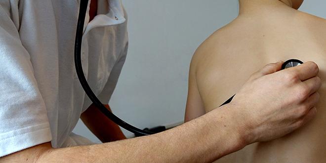 Доктор стетоскопом врши медицински преглед плућа малог дечака