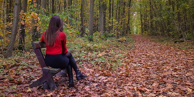 Јесен, девојка седи на клупи у шуми
