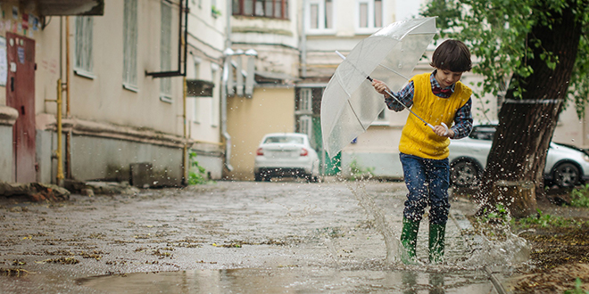 Kiša, dečak sa kišobranom skače po barama na ulici