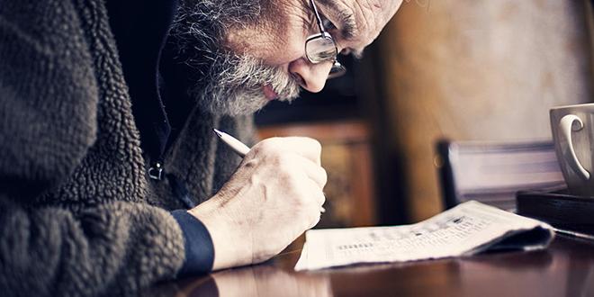 Stariji muškarac rešava ukrštenicu u novinama