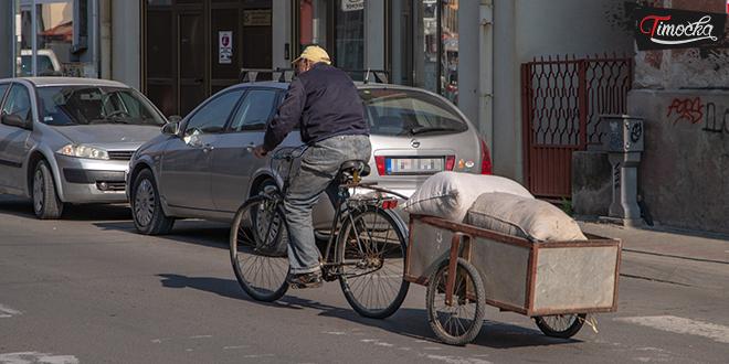 Stariji muškarac vozi bicikl sa malom prikolicom