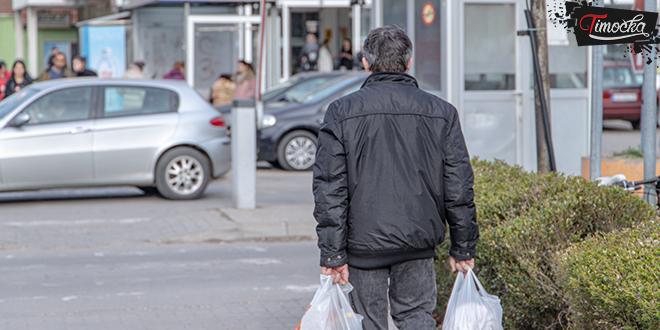 Muškarac nosi kese iz prodavnice