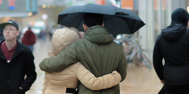 Zagrljeni par sa kišobranom šeta po kiši