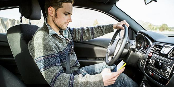 Muškarac drži mobilni telefon dok vozi automobil