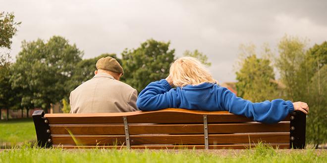 Muškarac i žena sede na klupi u parku